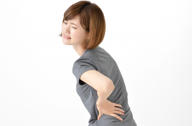 背中を抑える女性の写真