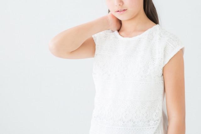 首を抑える女性の写真