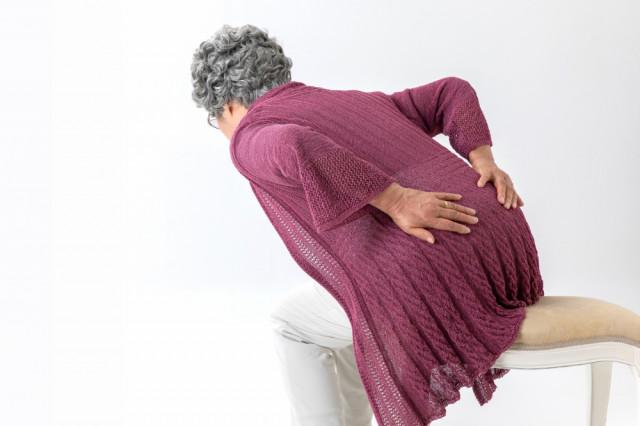 腰を抑える女性の写真